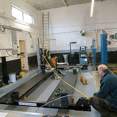 Lift engineers accurately measure the precise position fo rthe new vehicle lift.