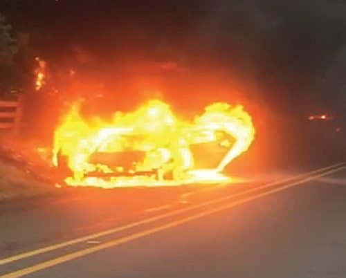 Burning vehicle at side of road