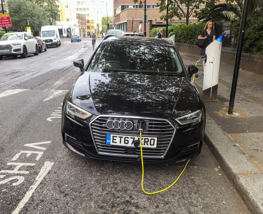 An electric vehicle being charged at a roadside charging point.