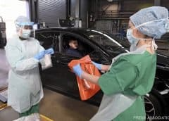 Medical staff demonstrate how they take samples at an MOT testing centre in Belfast, Northern Ireland